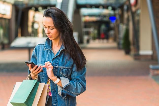 Signora con i sacchetti della spesa che utilizza smartphone nel centro commerciale