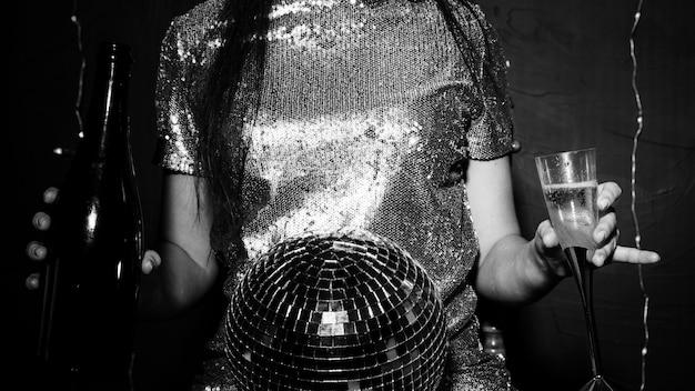 Signora con palla da discoteca, bottiglia e bicchiere