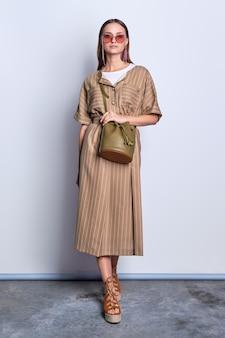 Signora d'avanguardia in grandi occhiali da sole che porta vestito verde oliva a strisce con la borsa di cuoio che posa sopra il fondo grigio