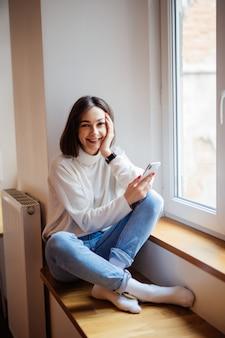 Signora dai capelli corti sorridente in blue jeans che si siedono sul davanzale e che scrivono messaggio sullo smartphone a casa