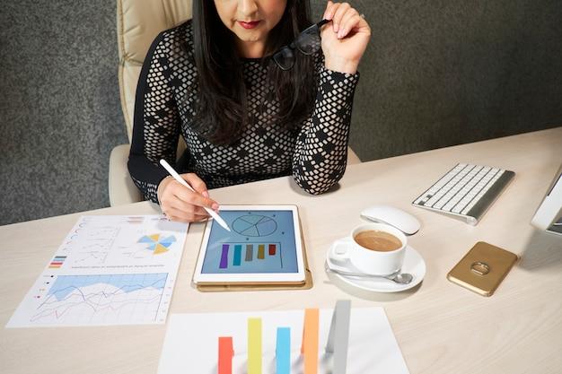 Signora di affari che analizza le statistiche finanziarie