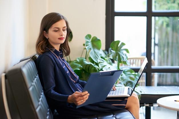 Signora di affari con il computer portatile e la lavagna per appunti