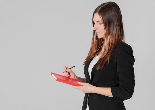 Signora di affari della donna in vestito nero con il pianificatore rosso del diario a disposizione