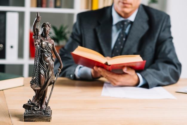 Signora di giustizia davanti al libro di legge della lettura della giustizia maschio