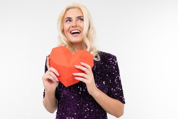 Signora di sogno felice in vestito viola che tiene cuore rosso di carta su fondo bianco con lo spazio della copia