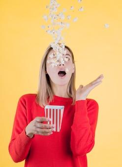 Signora di vista frontale che fa scivolare popcorn saporito