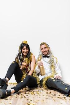 Signora e ragazzo ridenti in abiti da sera e orpelli con bottiglia e bicchiere sul pavimento