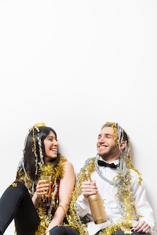 Signora e ragazzo ridenti in abiti da sera e orpelli con bottiglia e bicchiere