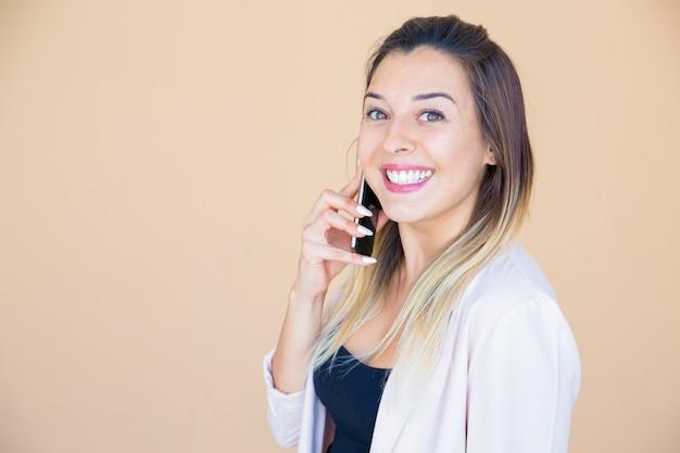 Signora emozionante felice che gode della conversazione telefonica