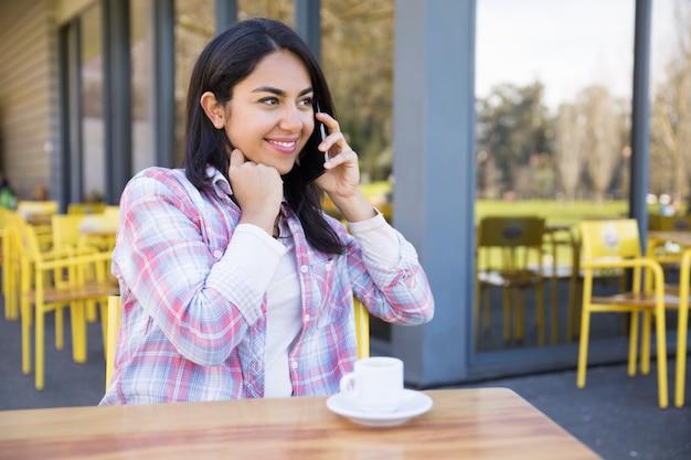 Signora felice che comunica sul telefono e che beve caffè in caffè della via