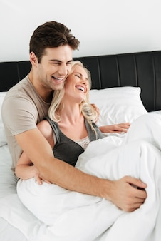 Signora felice che sorride mentre giace a letto con il suo uomo