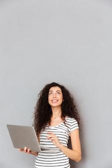 Signora felice con il messaggio di battitura a macchina dei capelli ricci o che comunica in internet facendo uso del computer portatile d'argento che è isolato sopra la parete grigia