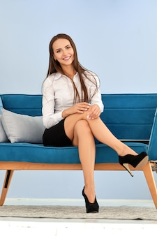Signora felice di affari che si siede sul sofà