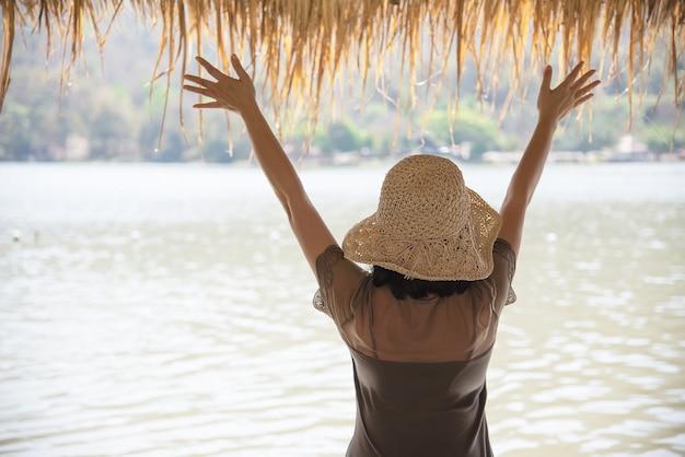 Signora felice durante la vacanza alla natura del sito dell'acqua
