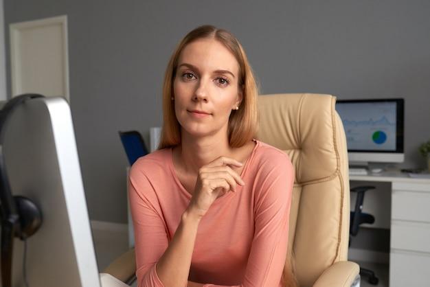 Signora graziosa di affari messa in poltrona comoda del capo nel suo ufficio