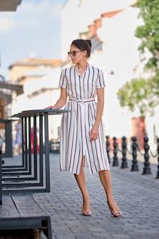 Signora graziosa in vestito a strisce nella città nel giorno soleggiato