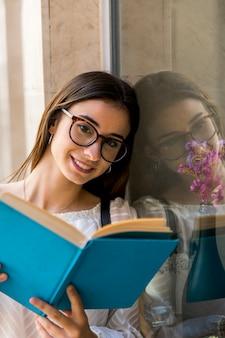 Signora guardando la fotocamera e tenendo il libro vicino alla finestra