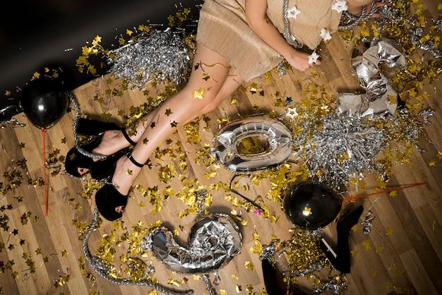 Signora in abiti da sera sul pavimento tra numeri di palloncini e orpelli