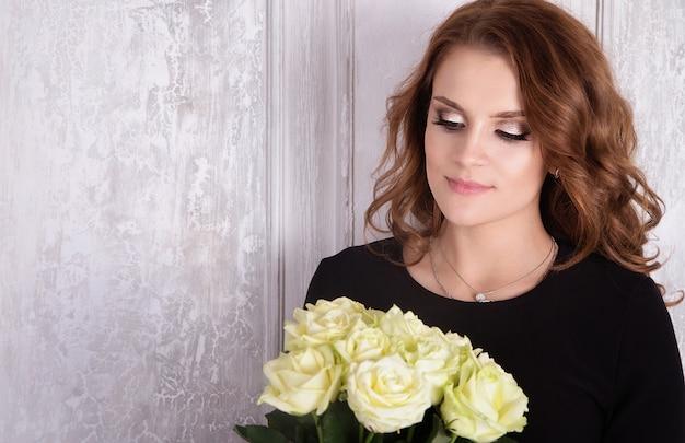 Signora in abito nero e rose bianche