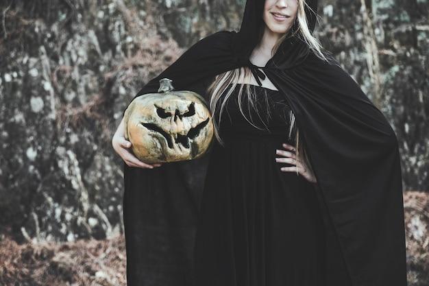 Signora in costume della strega che tiene zucca spaventosa