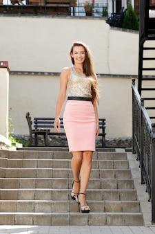 Signora in gonna rosa scendendo le scale
