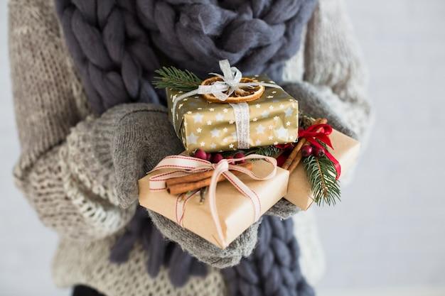Signora in guanti con un mucchio di scatole regalo in mano