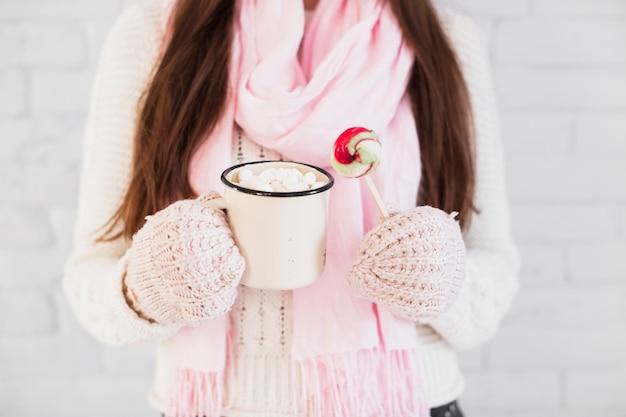 Signora in guanti e sciarpa tenendo la tazza con marshmallow e lecca-lecca