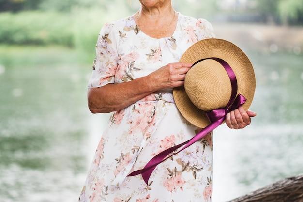 Signora in possesso di un cappello con un nastro in mano, camminando nel parco in una giornata di sole estivo, data, amore