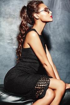 Signora modello bella donna sexy con labbra rosse in abito elegante nero seduto sul divano vicino alla parete grigia