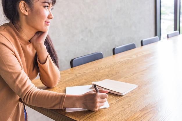 Signora pensante con penna e quaderni