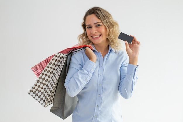 Signora positiva che mostra la carta di sconto e che tiene i sacchetti della spesa