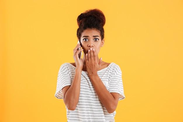 Signora scioccata parlando al telefono