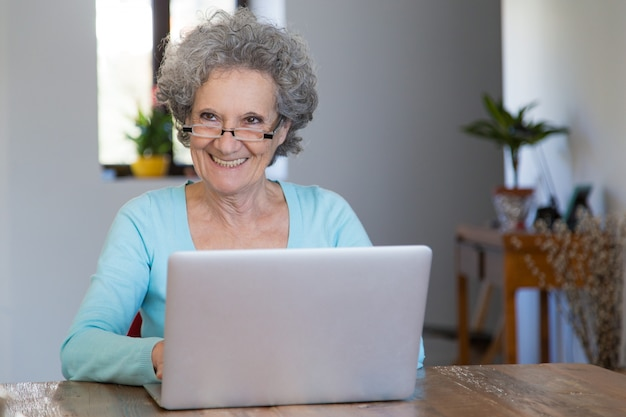 Signora senior allegra che utilizza i servizi online