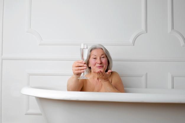 Signora senior che ha un bagno