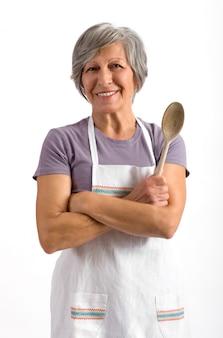 Signora senior che tiene un cucchiaio di legno