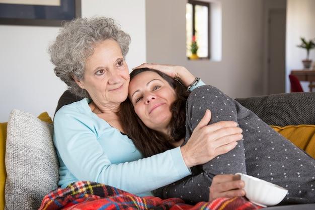 Signora senior pensierosa contenta che abbraccia figlia adulta