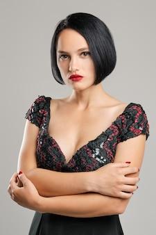 Signora seria con capelli corti scuri e labbra rosse che sembrano dritte leggermente arroganti.