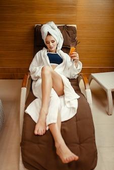Signora sexy in accappatoio e asciugamano sulla testa rilassante con un cocktail sulla sedia spa.
