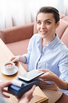 Signora soddisfatta positiva seduta al bar e bere il tè mentre si utilizza l'app mobile per il pagamento al ristorante