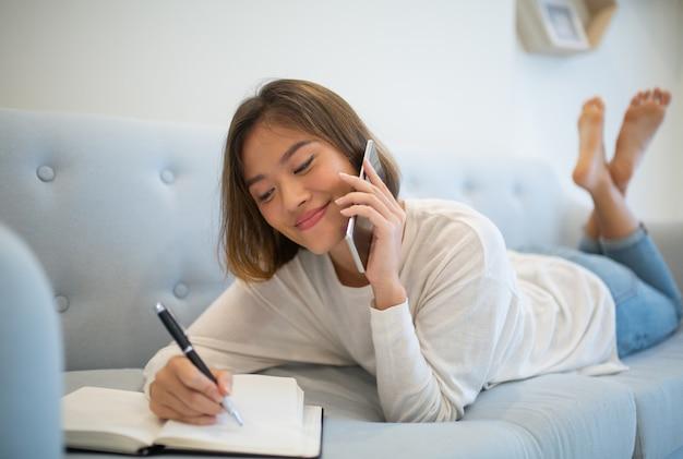 Signora sorridente che fa le note e che parla sul telefono a casa