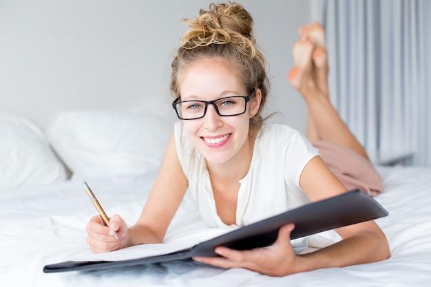 Signora sorridente che lavora con il documento sul letto