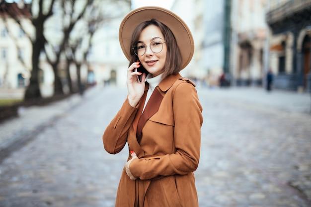 Signora sorridente in ampio cappello che parla sulla via di autunno dello smartphone