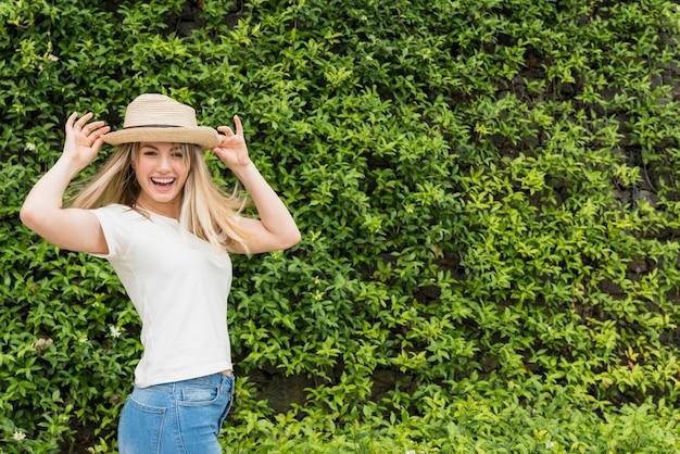 Signora sorridente in cappello vicino al cespuglio verde