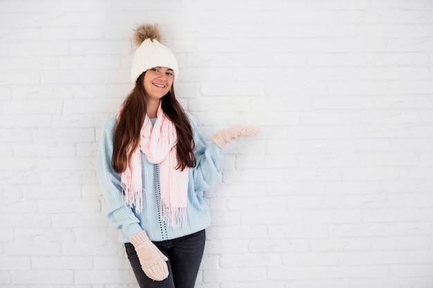 Signora sorridente in guanti, cappello bobble e sciarpa con la mano aperta