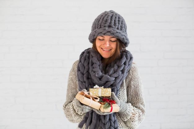 Signora sorridente in guanti, cappello e sciarpa con un mucchio di scatole regalo