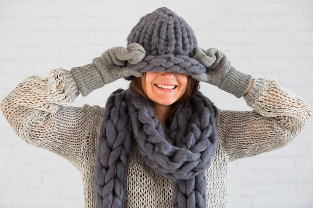 Signora sorridente in guanti, sciarpa e cappello sugli occhi
