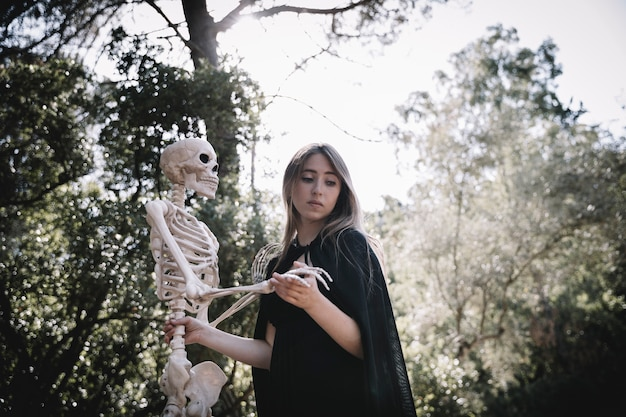 Signora spaventata in vestiti dello stregone che tengono scheletro