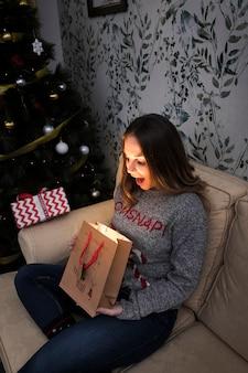 Signora stupita con pacchetto regalo sul divano vicino all'albero di natale