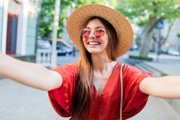 Signora sveglia in cappello alla moda che fa selfie mentre camminando all'aperto nei fine settimana estivi