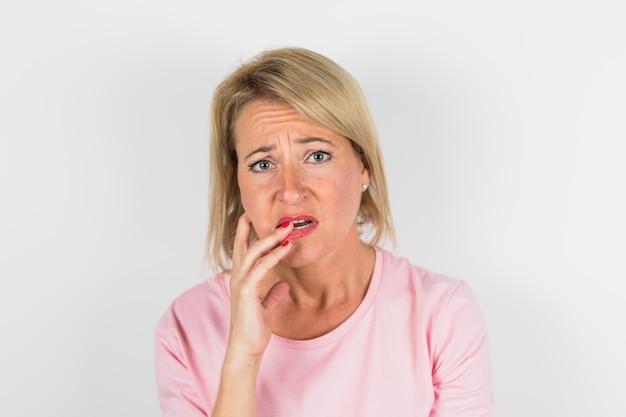 Signora triste invecchiata in camicia rosa